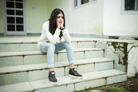 Outdoor image of Asian, sad girl looking down, thinking and sitting on steps by holding her head. She is in jeans and white sweater. One person, full length, horizontal composition with copy space.