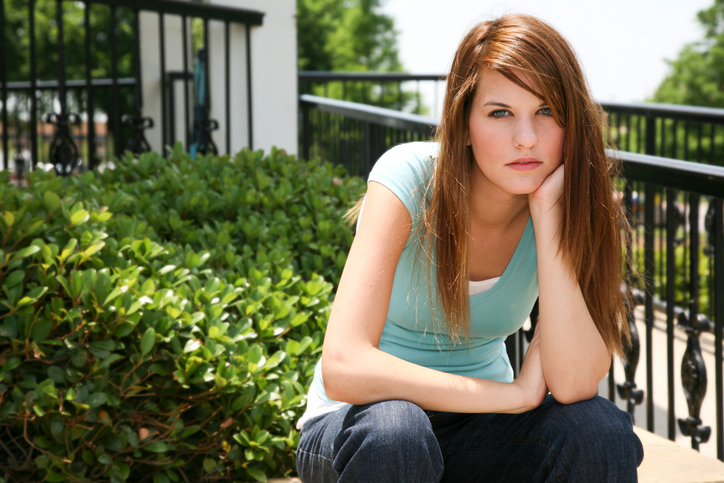 Serious College Aged Girl Sitting Down with Hand to Chin