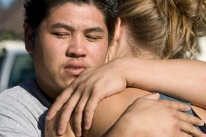 Young Man Hugging Girlfriend, Wondering How to Help an Alcoholic